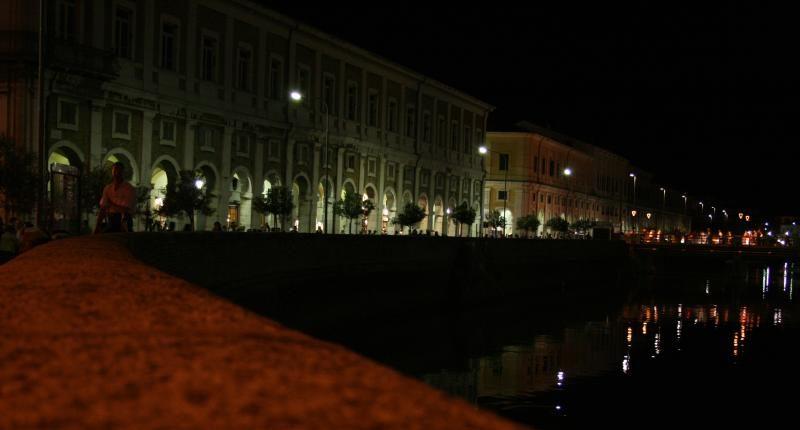 Vista notturna dal fiume verso i portici Ercolani illuminati
