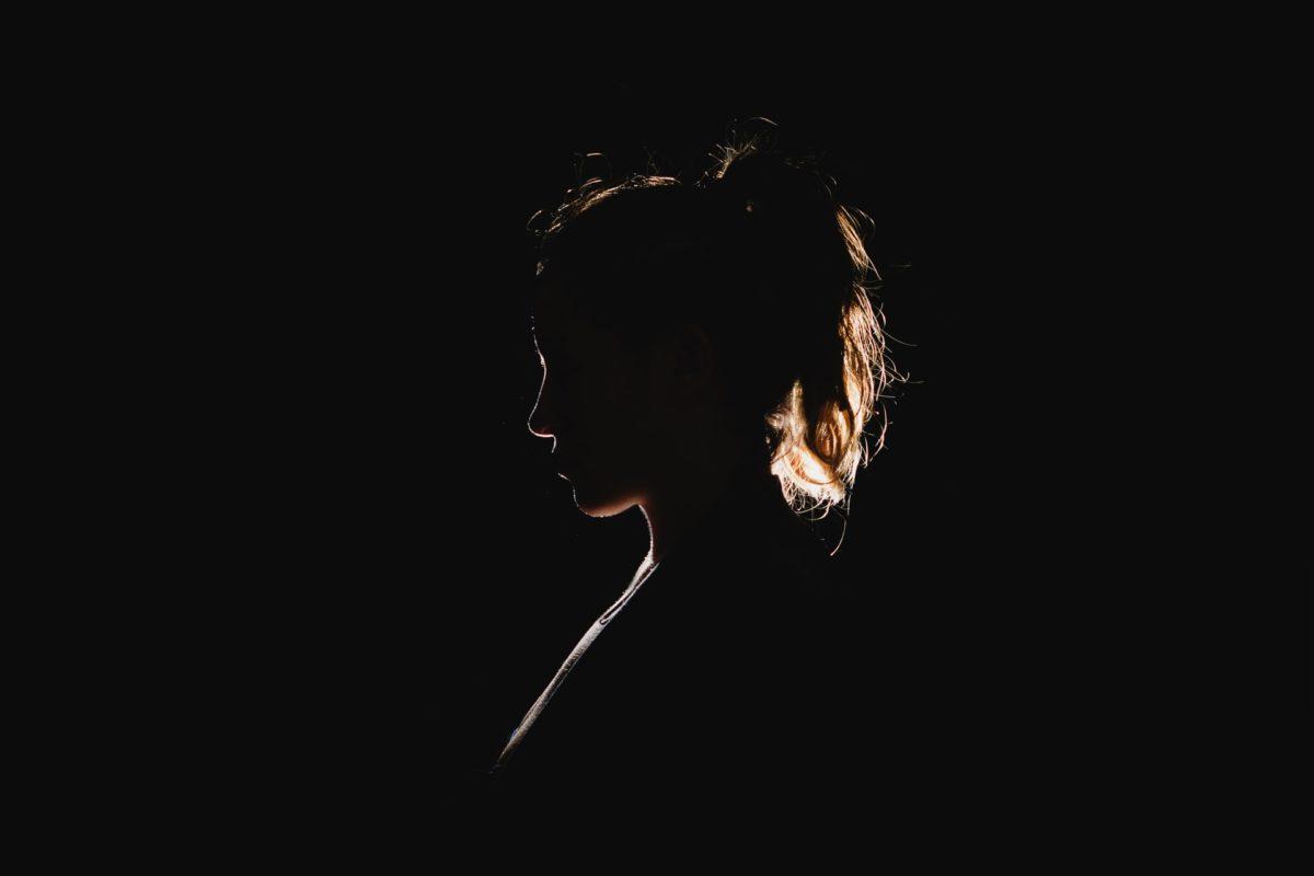 Nell'immagine, la silouhette di una giovane donna in controluce.